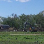 Backhoe at Swier dairy site, apparently amid clearing old buildings