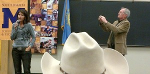 Rep. Kristi Noem speaks at a town hall meeting; Rapid City Journal reporter Kevin Woster snaps a picture.