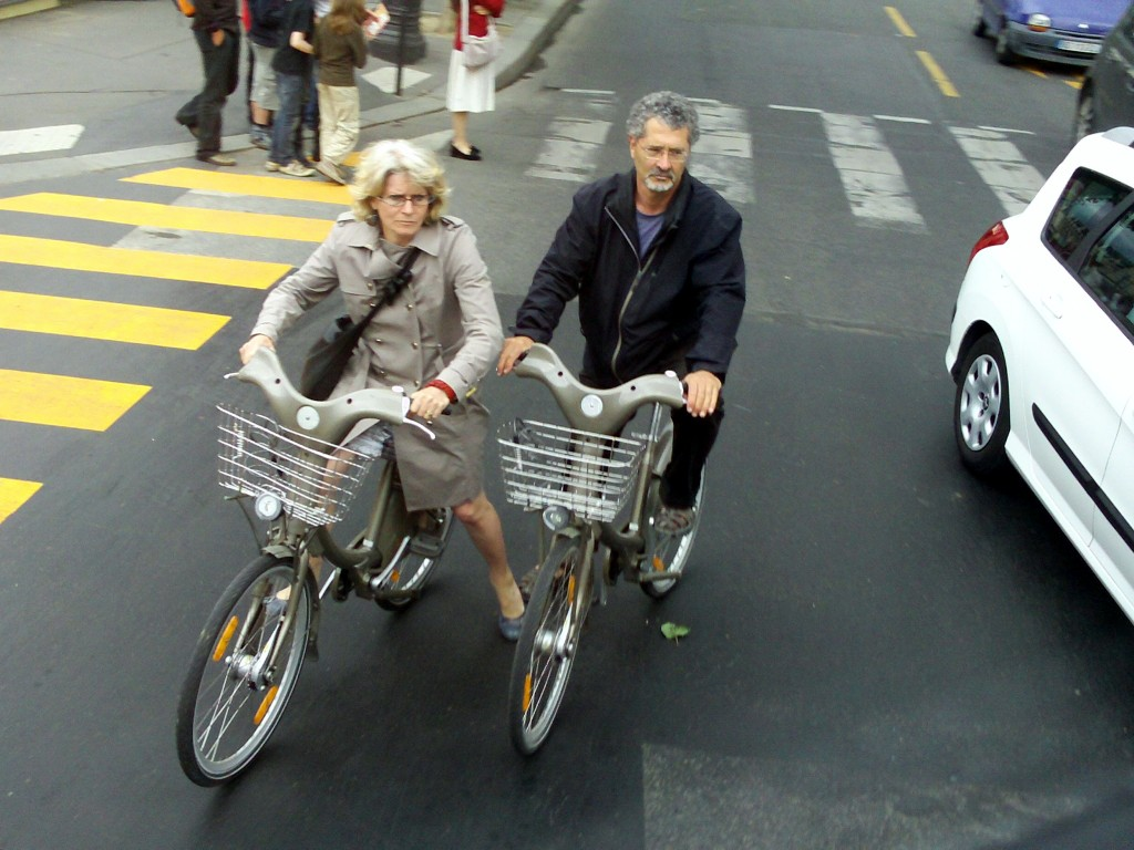 Couple on City Bikes in downtown Paris traffic