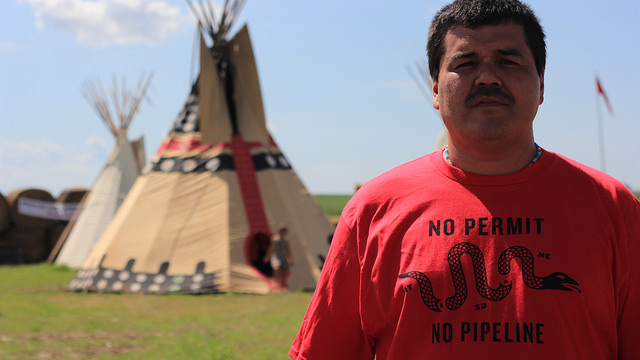 "Protestor proudly sports ""No Permit, No Pipeline"" logo at  Cowboy and Indian Alliance buffalo roast at the Oyate Wahacanka Woecun Rosebud Sioux Spirit Camp near Ideal, South Dakota on June 27, 2014. Photo by Matt Sloan for Bold Nebraska."